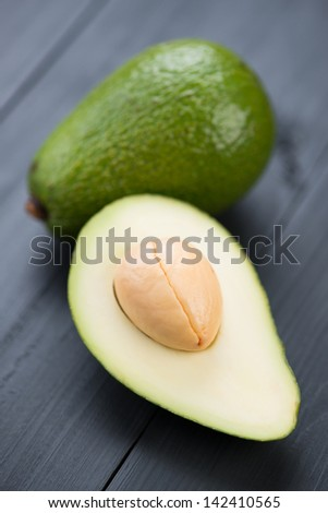 Ripe avocado and its half on black wooden boards, vertical shot