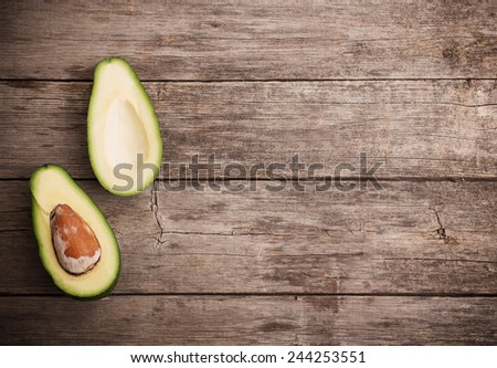 Ripe avocado on a wooden background - stock photo