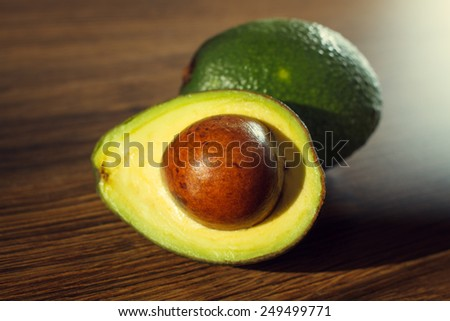Ripe avocado on a wooden background.Whole and half fruit - stock photo