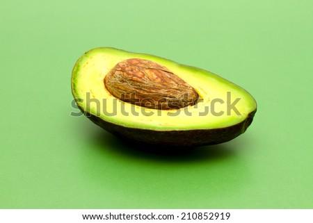 Ripe avocado on green background - stock photo