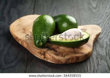 ripe avocados on olive cutting board - stock photo