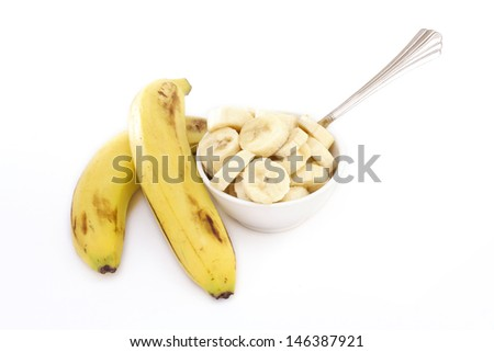 Ripe banana and bowl of slices