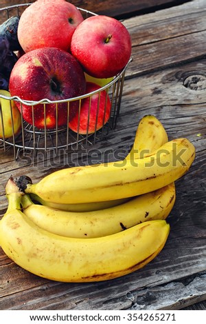 Ripe bananas and the apples in the barrel braided iron rods - stock photo