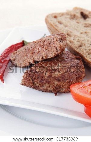 ripe beef meat hamburger on white plate with rye bun on white plate with cutlery on tablecloth