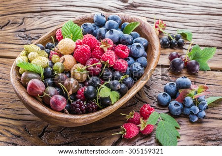Ripe berries in the wooden bowl on the table. - stock photo