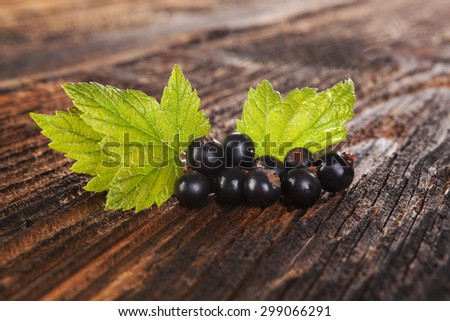 Ripe black currant on old vintage wooden background. Healthy summer fruit eating.  - stock photo