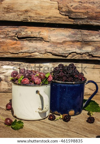Ripe blackberries and gooseberries in a metal mug on a wooden background closeup. Rustic style, selective focus