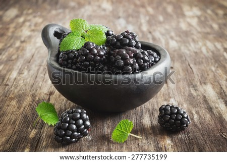 ripe blackberries in a bowl on the old wooden background. health and diet food. selective focus - stock photo