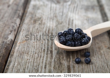Ripe blackberries in a wooden spoon on the table