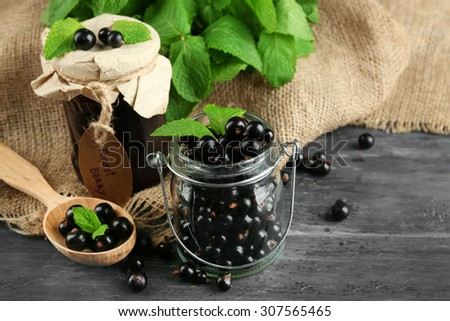 Ripe blackcurrant in glass jar and tasty jam on wooden background - stock photo