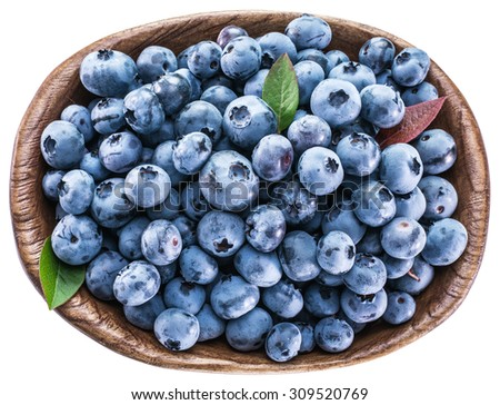 Ripe blueberries in the wooden bowl. Top view. File contains clipping paths. - stock photo