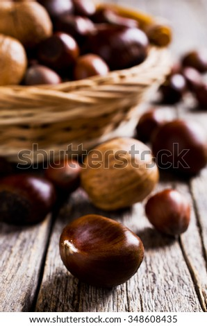 Ripe brown nuts on wooden surface. Selective focus.