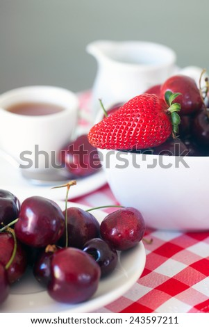 Ripe cherries and strawberries in a bowl. - stock photo