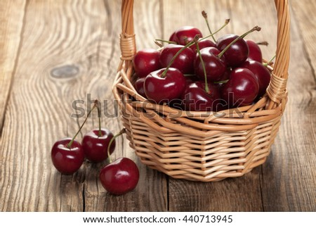 Ripe cherries in a basket on an old board