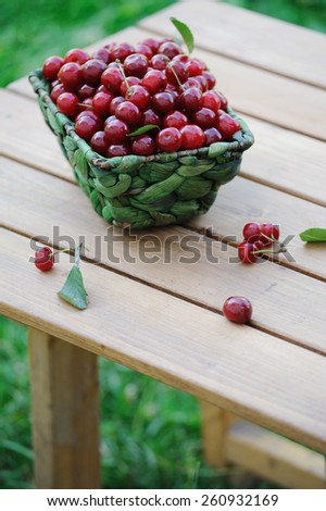 Ripe cherries in a basket on wooden table outdoor - stock photo