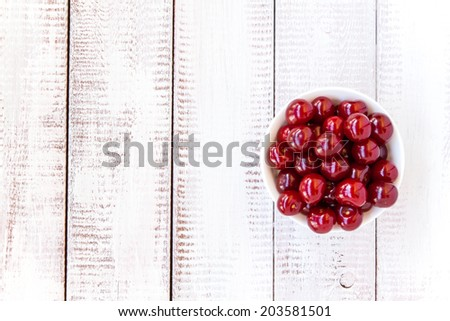 ripe cherries in a bowl on a white wooden rustic background - stock photo
