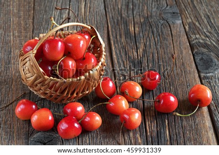 Ripe cherries in basket and near on dark wooden background