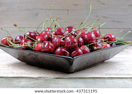 Ripe cherries in black porcelain plate on a old wooden table - stock photo