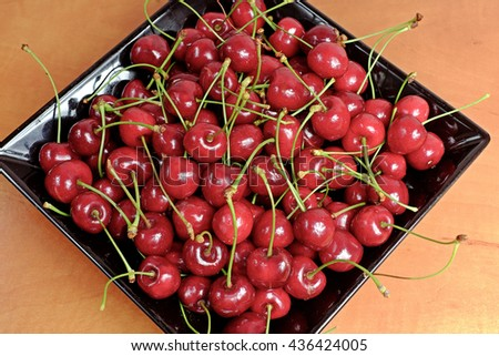 Ripe cherries in black porcelain plate on a wooden table - stock photo