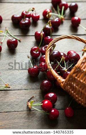 Ripe cherries in bulk on a table and a basket, food - stock photo