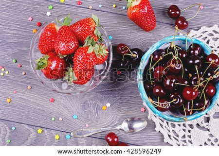 Ripe cherries in handmade clay bowl and strawberries on the background. Red ripe strawberries in the glass bowl near the cherry bowl on knitted napkin on the gray table.  - stock photo