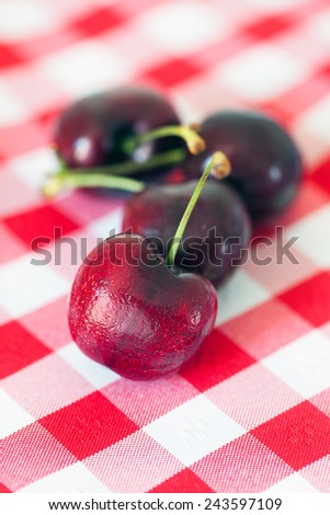 Ripe cherries on a checkered cloth. - stock photo