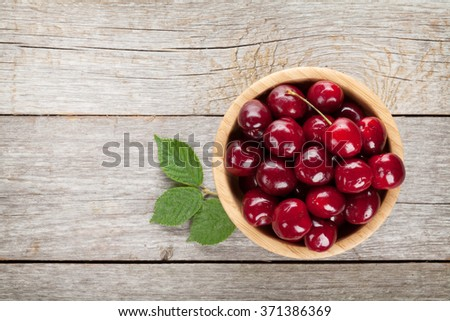 Ripe cherries on wooden table. View from above with copy space  - stock photo