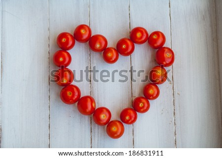 Ripe cherry tomatoes arranged in the form of heart - stock photo