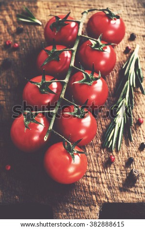 Ripe cherry tomatoes branch on rustic cutting board