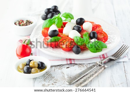 Ripe cherry tomatoes, fresh basil leaves, mozzarella cheese and olive oil for caprese salad on white wooden background, selective focus - stock photo