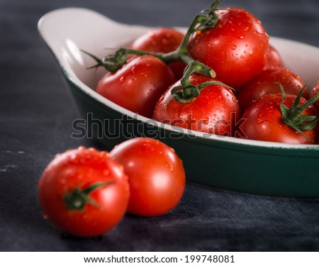 Ripe cherry tomatoes in a bowl on a black background - stock photo