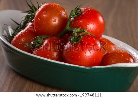 Ripe cherry tomatoes in a bowl on a wooden table - stock photo