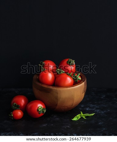 Ripe cherry-tomatoes in wooden bowl with basil leaves, spices and salt. Black background - stock photo