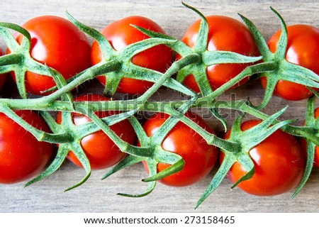 Ripe cherry tomatoes on the vine on a wooden surface - stock photo
