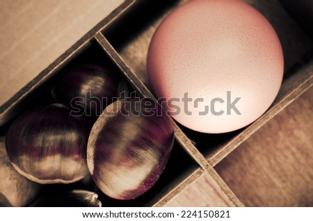 ripe chestnuts and egg in a wood box