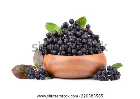 Ripe chokeberry or black rowanberry with green leaves in bamboo plate on white background