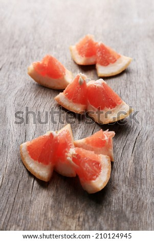 Ripe chopped grapefruit on wooden background - stock photo