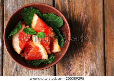 Ripe chopped grapefruit with mint leaves on plate, on wooden background - stock photo