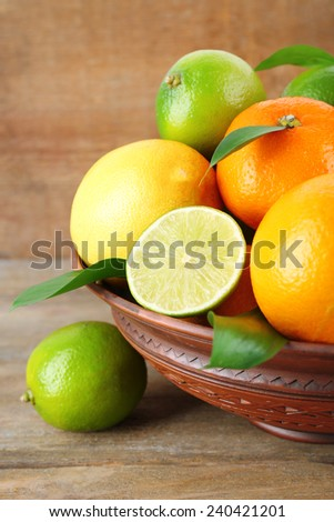 Ripe citrus with green leaves on plate on wooden background - stock photo