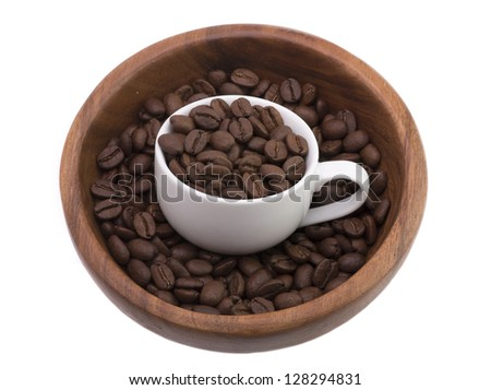 Ripe coffee beans are in a brown wooden bowl with a white cup.