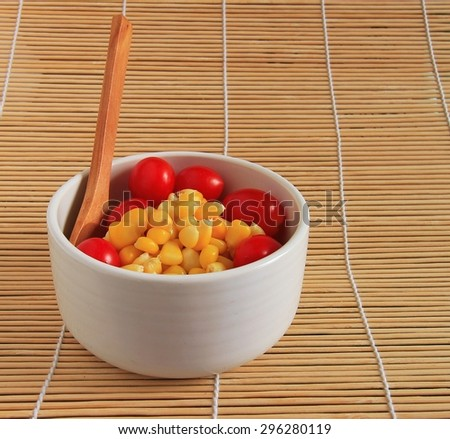 Ripe corn and tomatoes in bowl on a plate on the table - stock photo