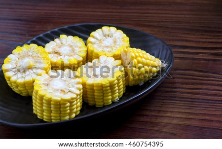 Ripe corn on cutting board on wooden background - stock photo