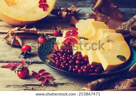 ripe cranberries and sliced pumpkin in a plate on old wooden table, vintage style. autumn motifs.health and diet food.selective focus - stock photo
