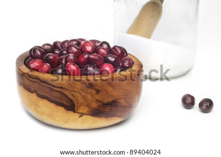 Ripe cranberries in a wooden bowl and a glass jar with sugar, isolated - stock photo