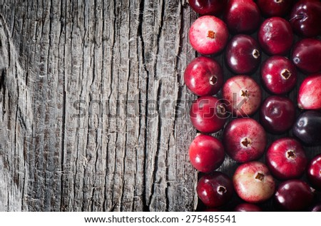 Ripe cranberry on an old wooden board with space for text - stock photo