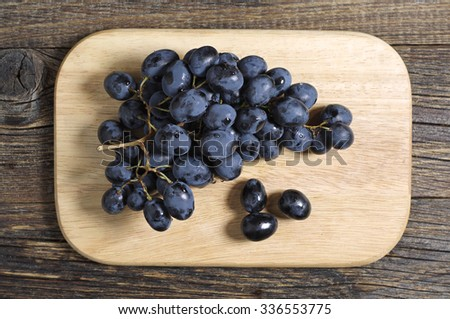 Ripe dark grapes on rustic wooden table, top view - stock photo