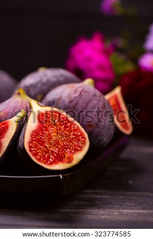 Ripe delicious figs and autumn flowers on black wooden background. Selective focus. Toned image