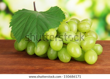 Ripe delicious grapes on table on bright background - stock photo