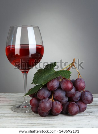 Ripe delicious grapes with glass of wine on table on gray background