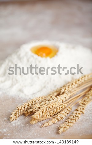 Ripe ears of wheat in a bakery lying on a counter alongside measured flour with a broken egg on top conceptual of fresh ingredients for making bread - stock photo
